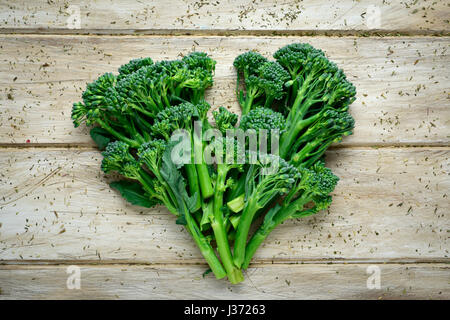 high-angle shot of some stems of broccolini forming a heart on a wooden rustic table - Stock Photo