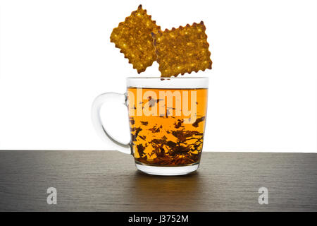 Glass cup of tea and falling cookies isolated on white - Stock Photo