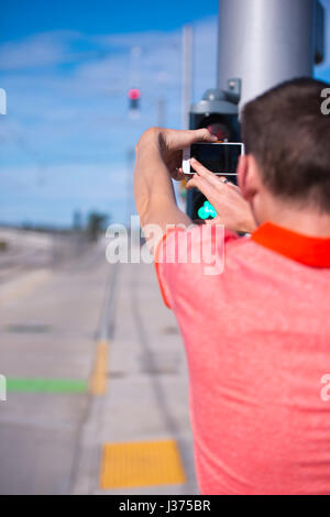 Young man in a red shirt taking pictures outside on the road on mobile smart cell phone with a large screen, which - Stock Photo