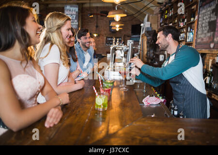 Cheerful bartender interacting with customers while making drink at bar - Stock Photo