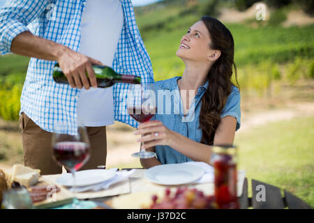 Smiling woman looking at man pouring red wine in glass at table - Stock Photo