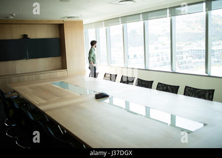 Thoughtful businessman looking through window in meeting room - Stock Photo