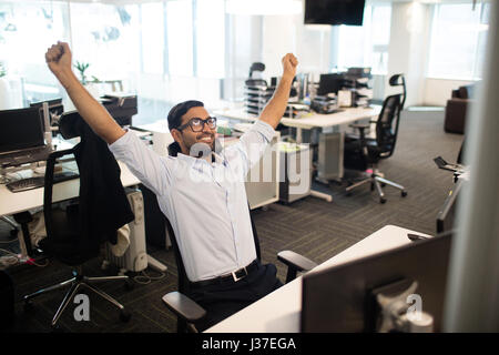 Happy businessman with arms raised sitting on chair in office - Stock Photo