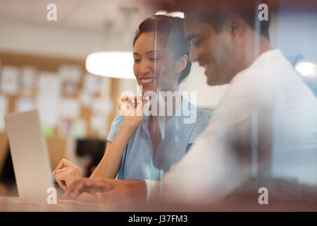 Happy business colleagues discussing while working in office seen through glass - Stock Photo