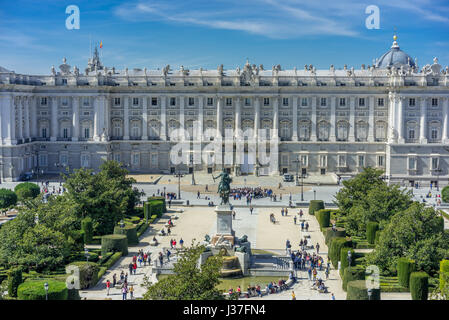 Tourists gathering around Prince's Gate of Royal Palace (Palacio Real) and Monument to Philip IV in Plaza de Oriente - Stock Photo