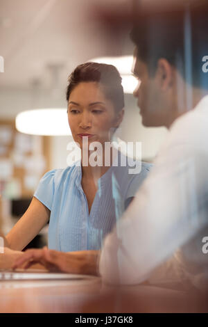 Business colleagues discussing while working in office seen through glass - Stock Photo