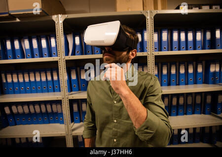 Businessman wearing VR glasses in file storage room at workplace - Stock Photo