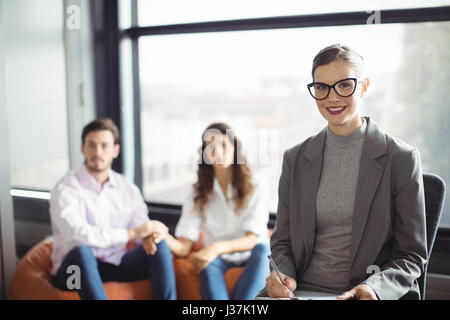 Portrait of smiling marriage counselor with couple in background - Stock Photo