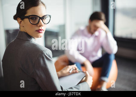 Portrait of counselor with man in background during therapy - Stock Photo