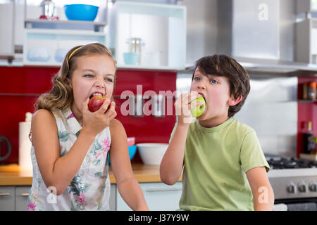 Siblings eating apple in kitchen at home - Stock Photo