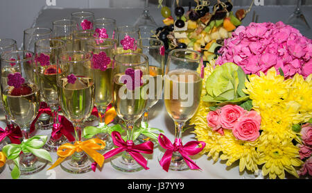 Festive table. Glasses of champagne decorated with ribbons. Bunch of flowers. Fruit snacks - Stock Photo