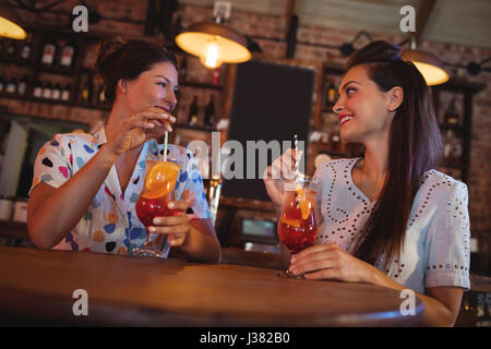 Two young women having cocktail drinks in pub - Stock Photo