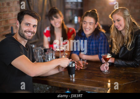 Portrait of handsome bartender making drinks for customers in bar - Stock Photo