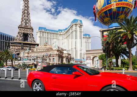 A red convertible rental car drives by Paris Las Vegas Hotel on Las Vegas Boulevard - Stock Photo