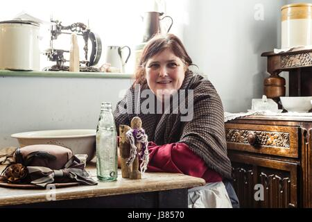A woman poses in Victorian dress in the squatters cottage at Blists Hill Museum, Ironbridge, UK - Stock Photo