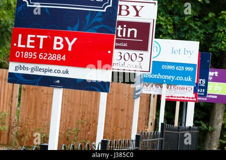 Estate agent 'let by' signs advertise property in a suburb of London - Stock Photo
