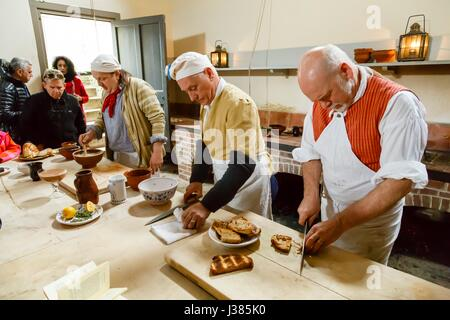 Chefs in traditional costume cooking in the Royal Kitchens, Kew Gardens, London, UK - Stock Photo