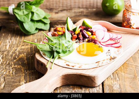 Fried egg tacos with chili con carne on rustic cutting board, Mexican traditional food - Stock Photo