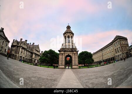 The Campanile on the campus quadrangle of Trinity College in Dublin near sunset as clouds clear prior to dusk descending - Stock Photo