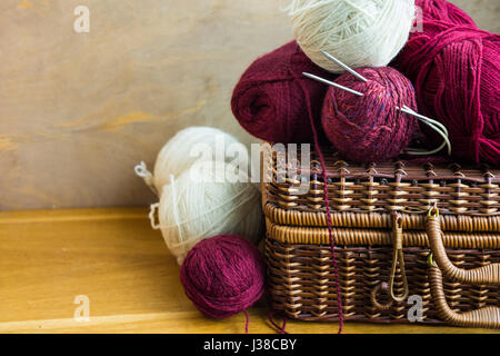 Vintage wicker basket balls clews of red white wool yarn, needles on wood table, knitting, crafts, hobby concept, - Stock Photo
