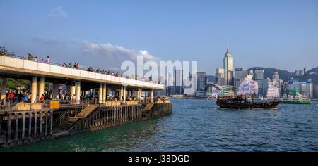 Tourists along the Tsim Sha Tsui promenade, and the newly designed dragon traditional Chinese junk, Victoria harbor, - Stock Photo