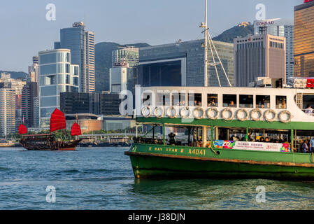 Traditional Chinese junk and Star ferry, with the Hong Kong financial district skyline, Victoria harbor, Hong Kong, - Stock Photo