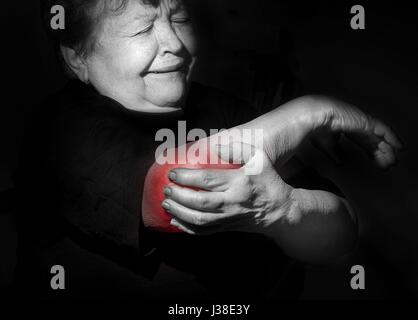 grandmother, old woman holding her arm, shoulder, elbow,  pain, distress, health problems, sport - Stock Photo