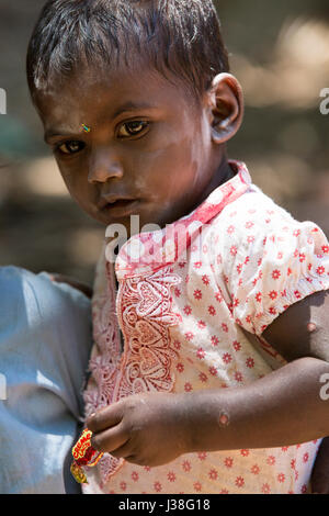 Documentary editorial image. Pondicherry, Tamil Nadu, India - June 15 2014. Very poor young boy in his sister arms. Poverty Stock Photo