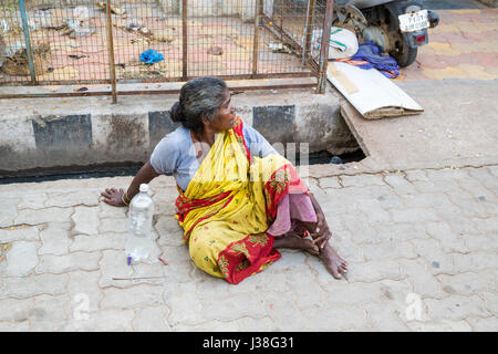 Documentary editorial image. Pondicherry, Tamil Nadu, India - June 23 2014. Very poor woman sitting in the street - Stock Photo