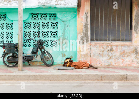 Documentary editorial image. Pondicherry, Tamil Nadu, India - June 24 2014. homeless and poor people writing, sleeping, walking in the street Stock Photo