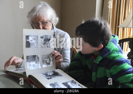 81 year old Grandmother and 12 year old grandchild looking at a photo album - Stock Photo