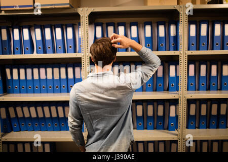 Rear view of confused businessman searching for files on cabinet in storage room - Stock Photo