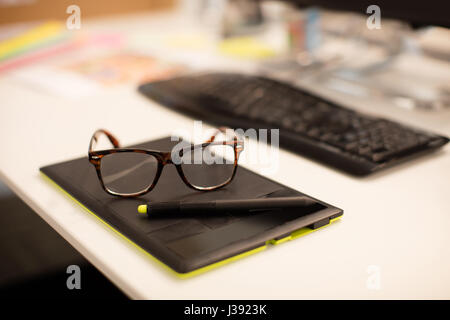 High angle view of eyeglasses on digitizer at desk in office - Stock Photo