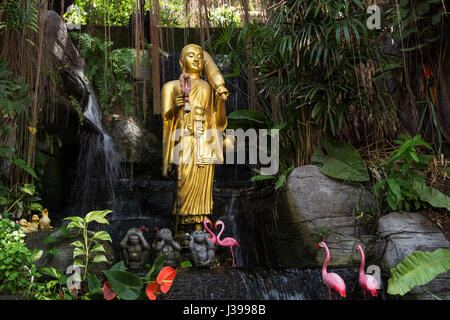 Golden Buddha statue and small artificial waterfall at the Golden Mount at Wat Saket in Bangkok, Thailand. - Stock Photo