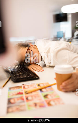 High angle view of tired businesswoman napping on desk at creative office - Stock Photo