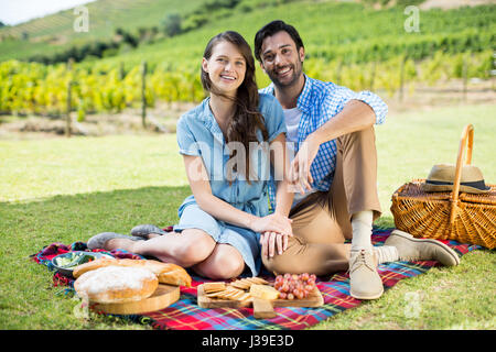 Portrait of happy couple sitting on picnic blanket with vineyard in background - Stock Photo