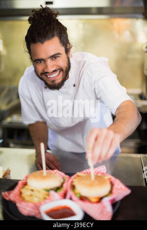 Portrait of happy male chef preparing burger in commercial kitchen - Stock Photo
