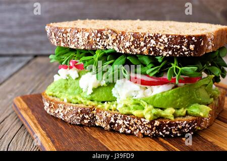 Superfood sandwich with whole grain bread, avocado, egg whites, radishes and pea shoots on wood board - Stock Photo