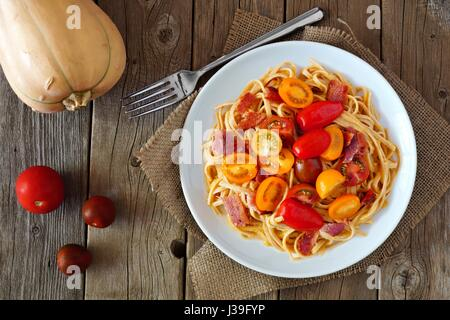 Creamy butternut squash pasta dish with bacon and cherry tomatoes, above view on rustic wood - Stock Photo