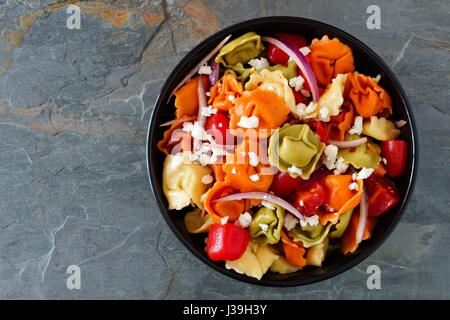 Colorful tortellini pasta salad with tomatoes and onions, overhead view on a dark slate background - Stock Photo