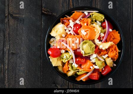 Bowl of multicolored tortellini pasta salad with tomatoes and onions, overhead view on a dark wood background - Stock Photo