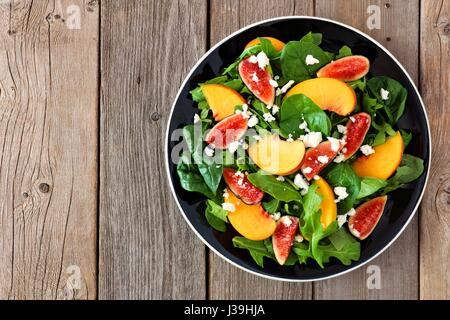 Autumn salad of arugula, spinach figs and goat cheese in a black plate, above view on a rustic wooden background - Stock Photo