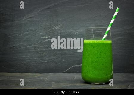 Green kale smoothie in a glass with straw on a dark slate stone background - Stock Photo