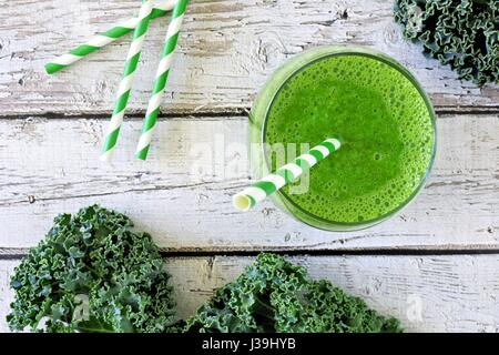 Green kale smoothie overhead view, in a glass with straw on an aged wood background - Stock Photo