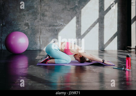 Side view of mature yogini stretching lower back and spine. Woman doing upward facing dog yoga pose. Woman practices - Stock Photo