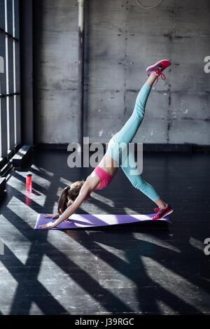 Beautiful sporty fit yogini woman practices yoga asana eka pada adhomukha svanasana - one-legged downward facing - Stock Photo