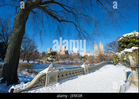 Scenic view from the landmark Bow Bridge of Central Park covered in snow on a bright winter morning after a storm - Stock Photo