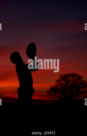Catching a rugby ball at sunset from a line out, playing schoolboy rugby