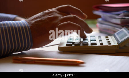 Accountant working long hours with stacks of paperwork and files, low light macro close up. - Stock Photo