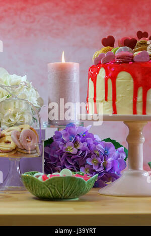 Mothers Day party table in feminine colour scheme with lilac gifts, flowers, pink candles and decadent cake decorated - Stock Photo
